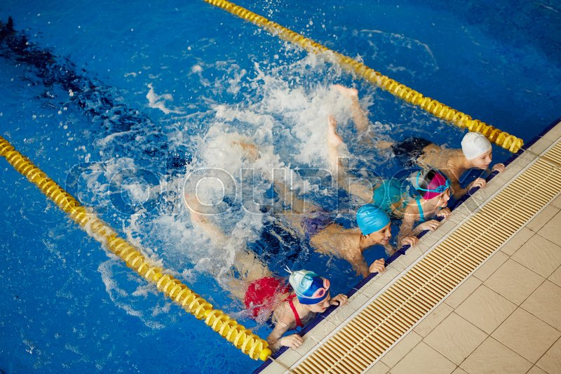 Row of active children splashing water in pool, stock photo