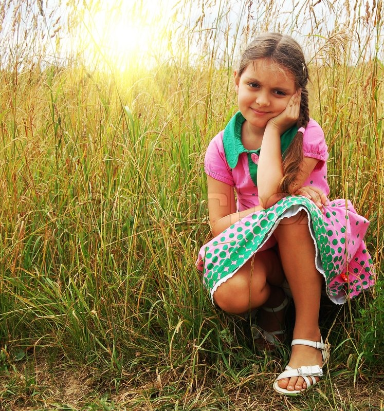 Cute Little Girl On The Meadow In Spring Day Stock Photo
