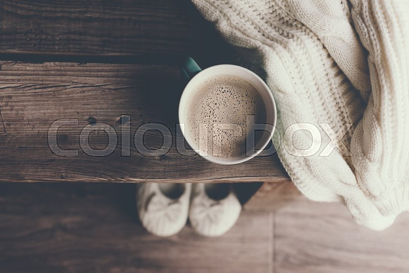 Cup of hot coffee on rustic wooden bench, closeup photo of warm sweater with mug and slippers, winter morning concept, top view, stock photo