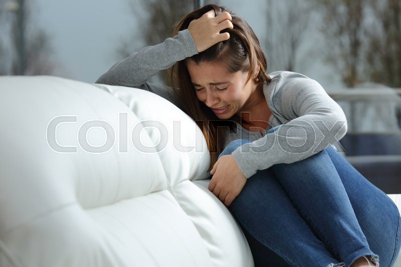 Sad girl crying desperately alone sitting on a couch at home in a dark winter day, stock photo