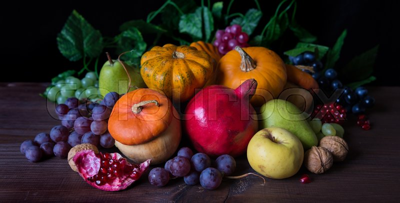 Autumn still life: decorative pumpkins, squash, apples, pears, pomegranates and grapes on the dark wooden background, stock photo
