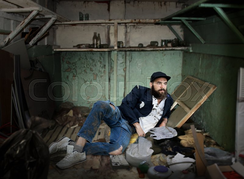 Vagrant lying in a dirty room, stock photo