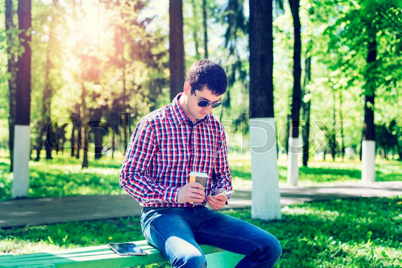The man in the summer in park, relaxing with a cup of coffee or tea, reading a sms on phone wearing glasses, reading news feeds in social networks, in jeans bright sunny day. Idea concept businessman breakfast, stock photo
