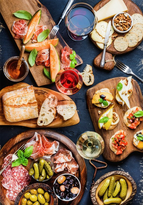 Italian antipasti wine snacks set. Brushettas, cheese variety, Mediterrnean olives, pickles, Prosciutto di Parma with melon, salami and wine in glasses over black grunge background. Top view, copy space, stock photo