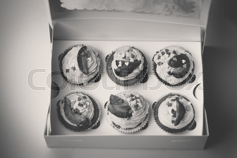 Closeup black and white photo of open box with 6 cupcakes with strawberry, stock photo