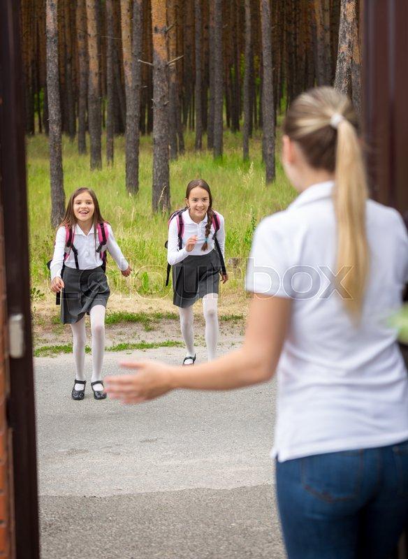 Young mother meeting her daughters after school in doorway, stock photo