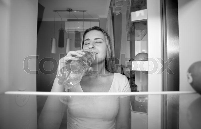 Black and white portrait of beautiful smiling woman taking water from fridge and drinking it. View from inside of open refrigerator, stock photo