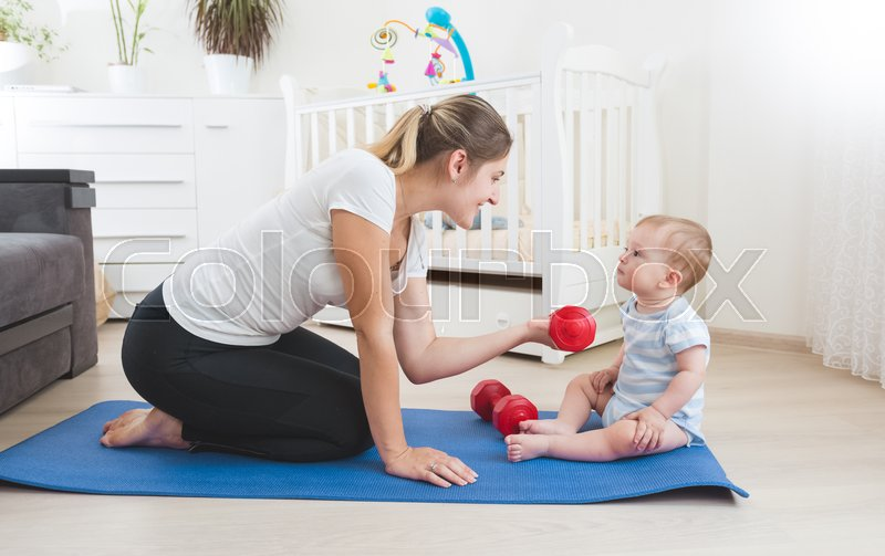 Beautiful smiling mother doing physical exercise with her baby on floor at living room, stock photo