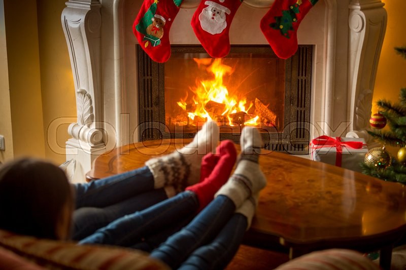 Closeup image of family in cosy knitted socks warming at fireplace ...
