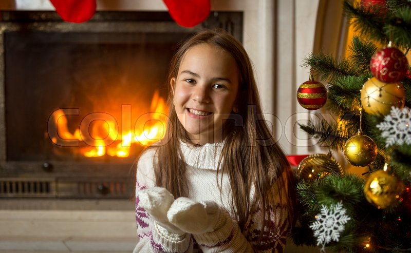 Portrait of happy smiling girl in sweater and gloves posing at burning fireplace and decorated Christmas tree, stock photo