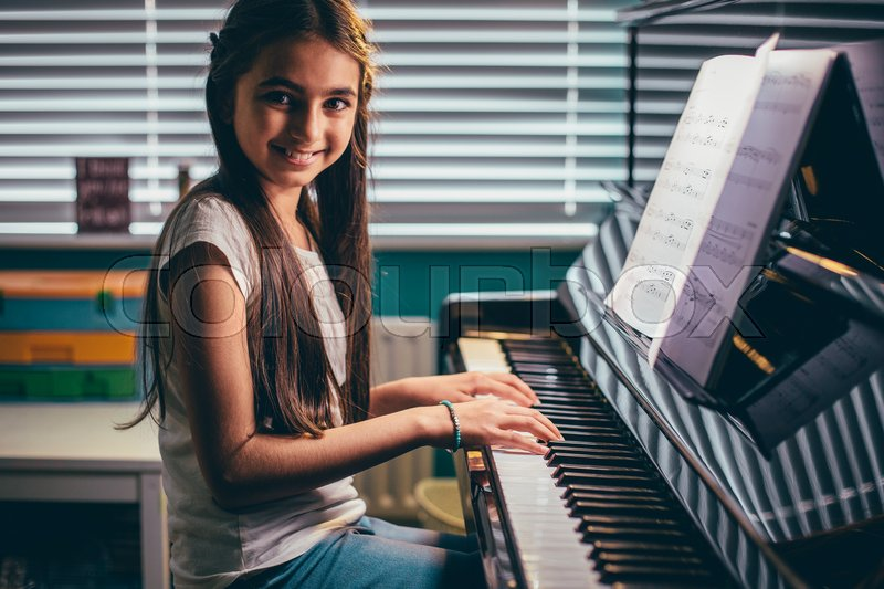 Happy girl smiling for the camera as she plays piano in her bedroom. , stock photo
