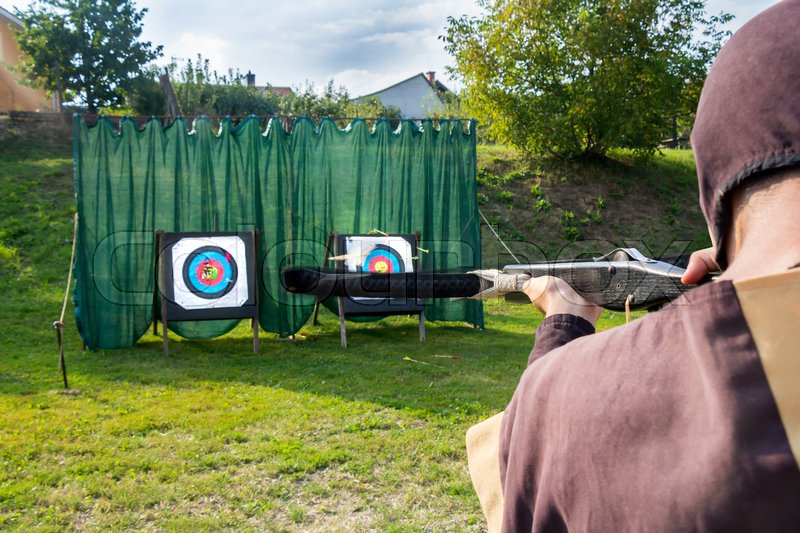 Medieval archer to use a crossbow and shoot at a target, stock photo