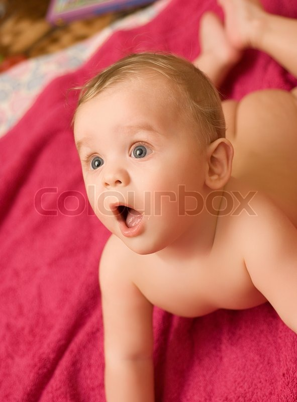 Lying baby boy at the pink bath towel | Stock Photo | Colourbox
