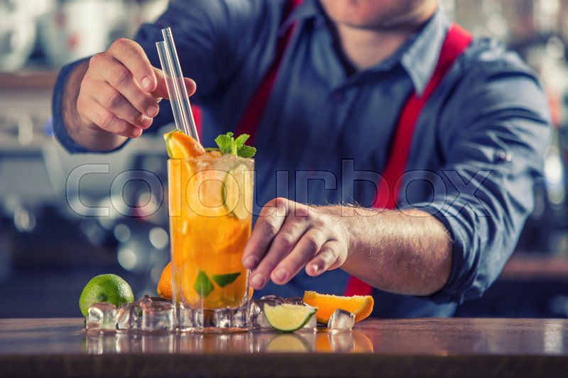 Mixed drink. Mixed alcoholic - non alcoholic cocktail. Barman Serving Drinks In Nightclub.Young barkeeper preparing drink, stock photo