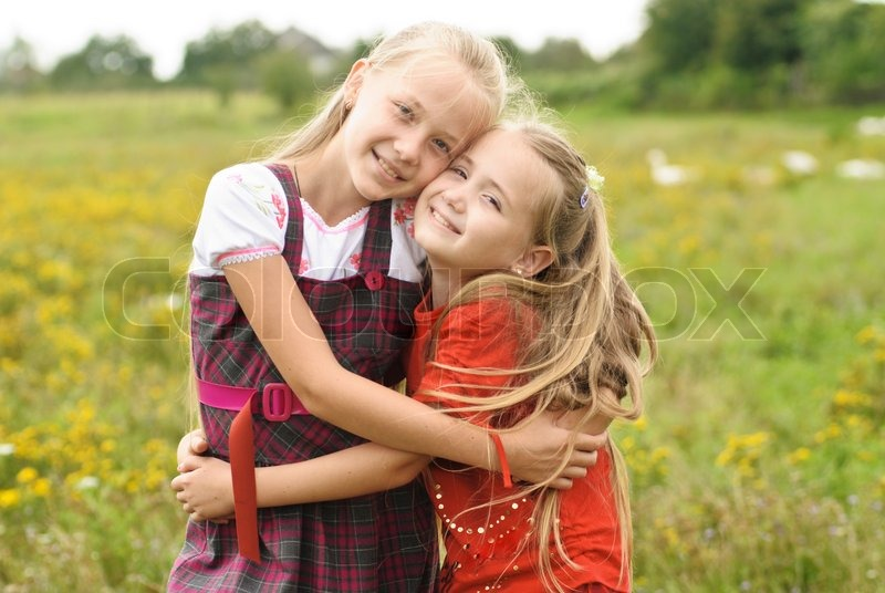 two sisters hug one another outdoors happy family stock photo