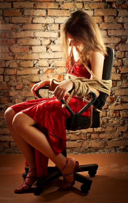 Woman tied up with a rope against brick wall stock photo colourbox