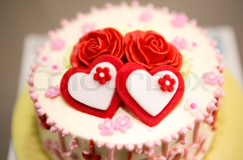 Close up and select focus on beautiful decorate cake with white and red heart , red roses , stock photo