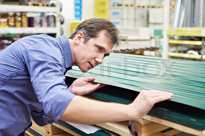 Man chooses metal profile for fence in construction store, stock photo