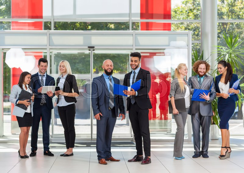 Business People Group Discussing Document Project Plan Communicating, Smile Talking In Modern Office, Businesspeople Colleague Team Over Glass Door, stock photo