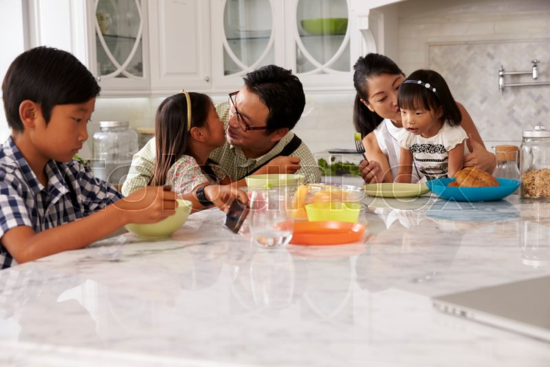 Father Leaving For Work After Family Breakfast In Kitchen, stock photo
