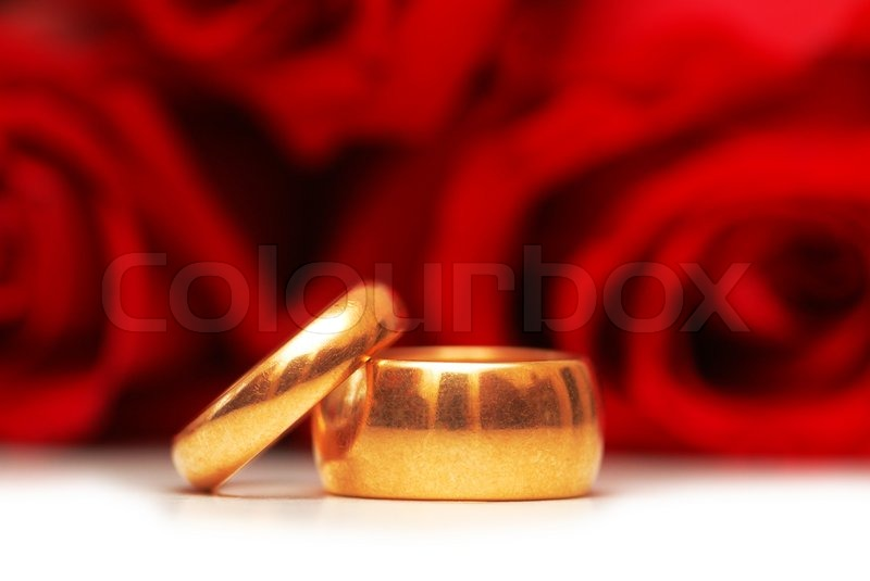 Wedding Rings And Roses At The Background Stock Photo