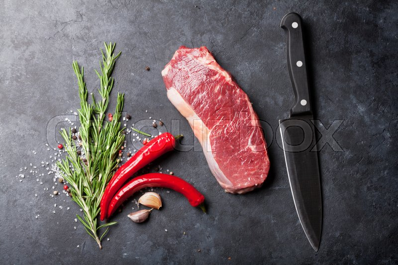 Raw striploin steak with rosemary, salt and pepper cooking over stone table. Top view, stock photo