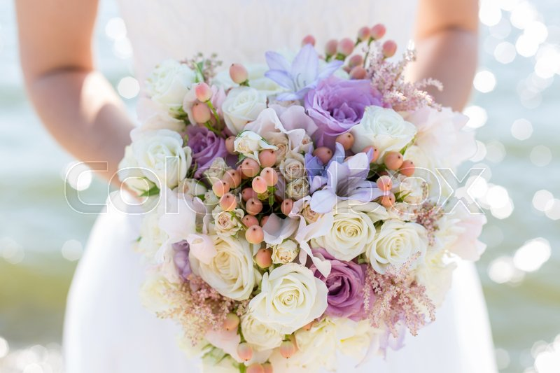 Wedding bouquet in hands of the bride, stock photo