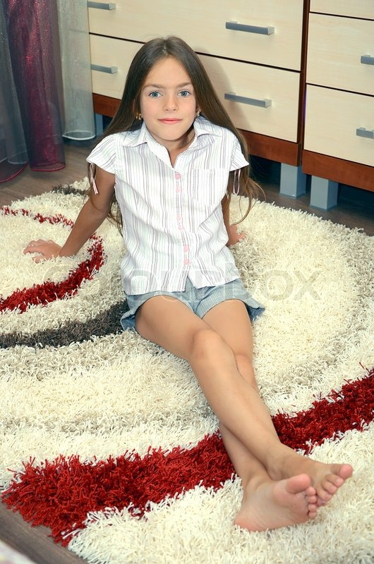 Girl Sitting On A Carpet Stock Photo Colourbox