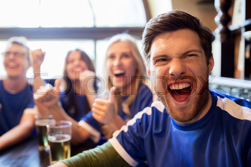 Sport, people, leisure, friendship and entertainment concept - happy football fans or friends drinking beer and celebrating victory at bar or pub, stock photo
