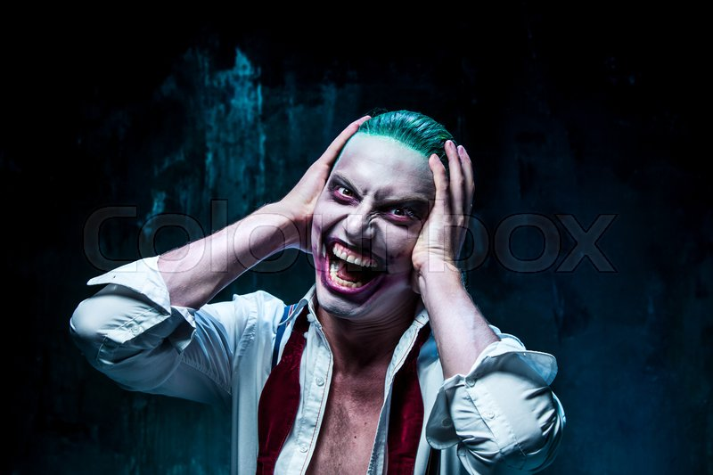 Bloody Halloween theme: The crazy joker face on black background, stock photo