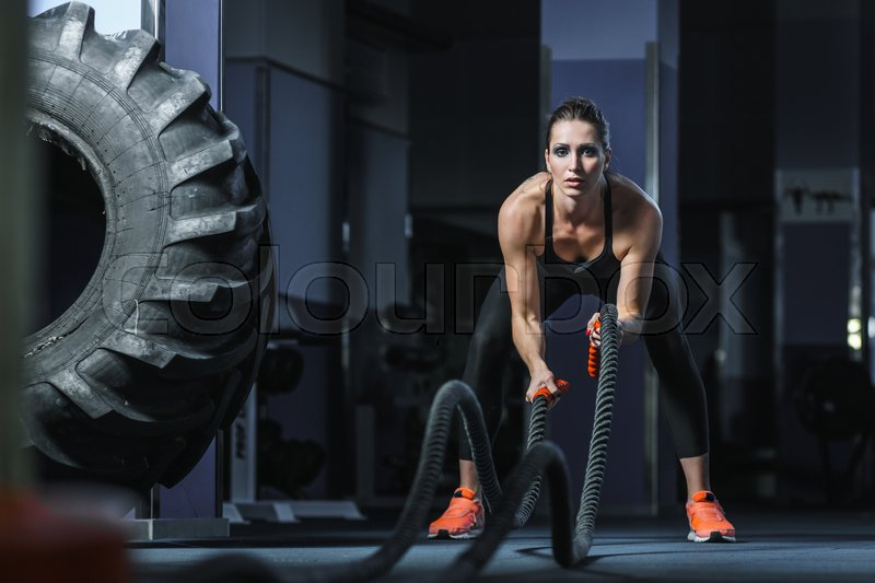 Concept: power, strength, healthy lifestyle, sport. Powerful attractive muscular woman CrossFit trainer do battle workout with ropes at the gym, stock photo