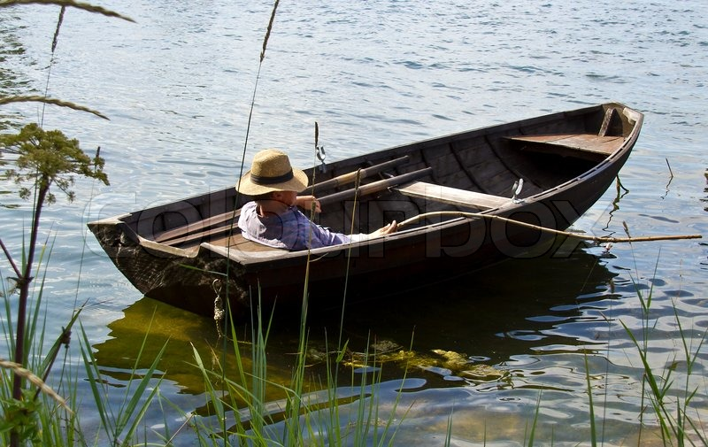 Fisherman relaxing in old row boat | Stock Photo | Colourbox