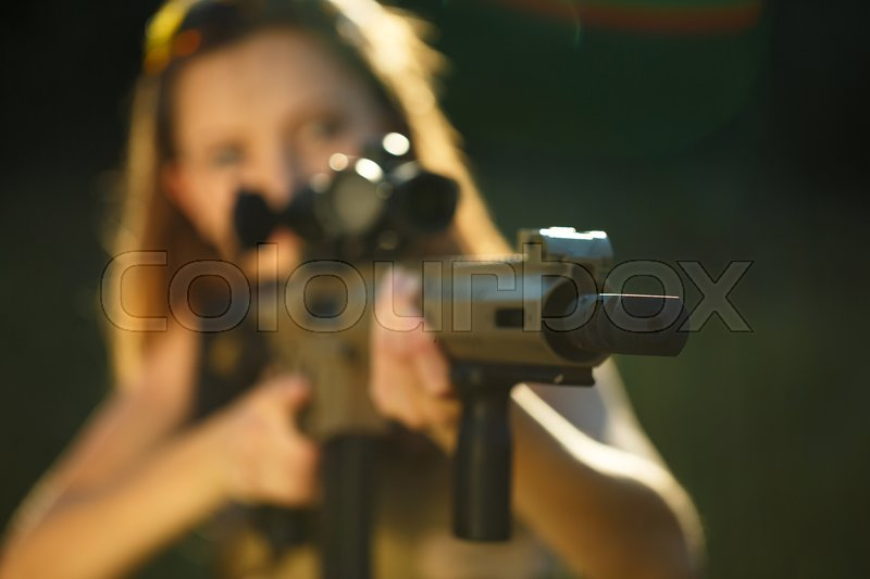A young girl with a gun for trap shooting aiming at a target. Short depth of field, focus on the barrel, stock photo