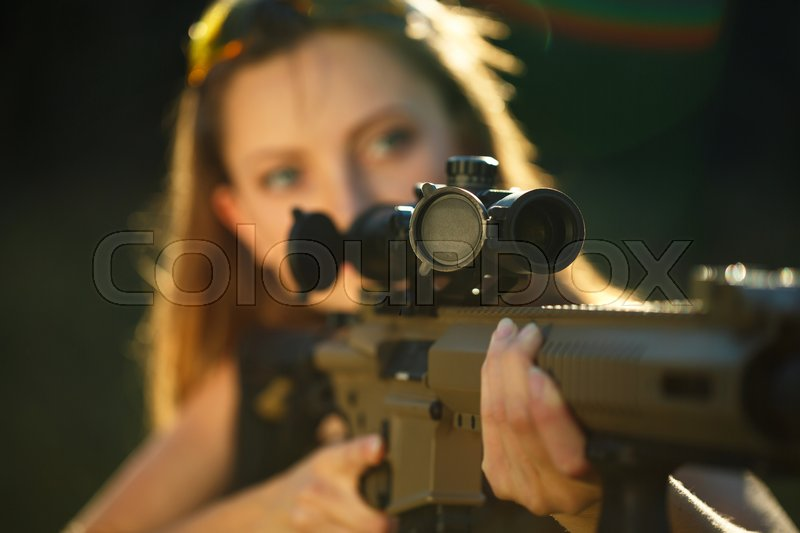 A young girl with a gun for trap shooting aiming at a target, stock photo