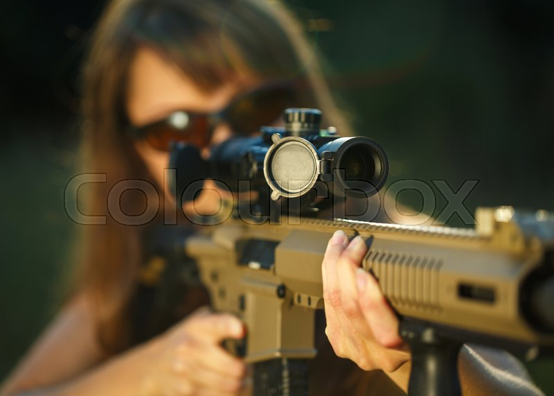 A young girl with a gun for trap shooting and shooting glasses aiming at a target, stock photo