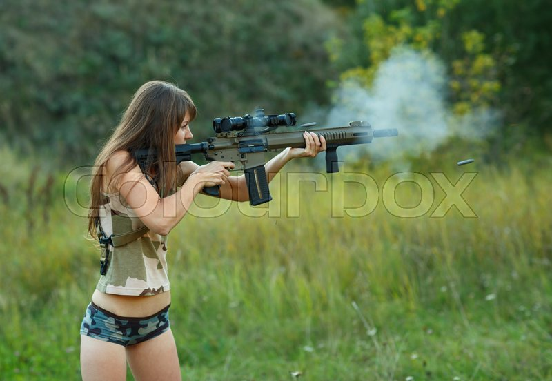 A young girl with a gun shooting at a target outdoors, stock photo