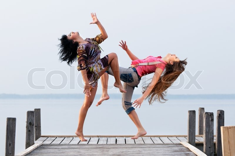 https://www.colourbox.com/preview/2130748-two-girl-are-dancing-on-background-of-water-and-sky.jpg