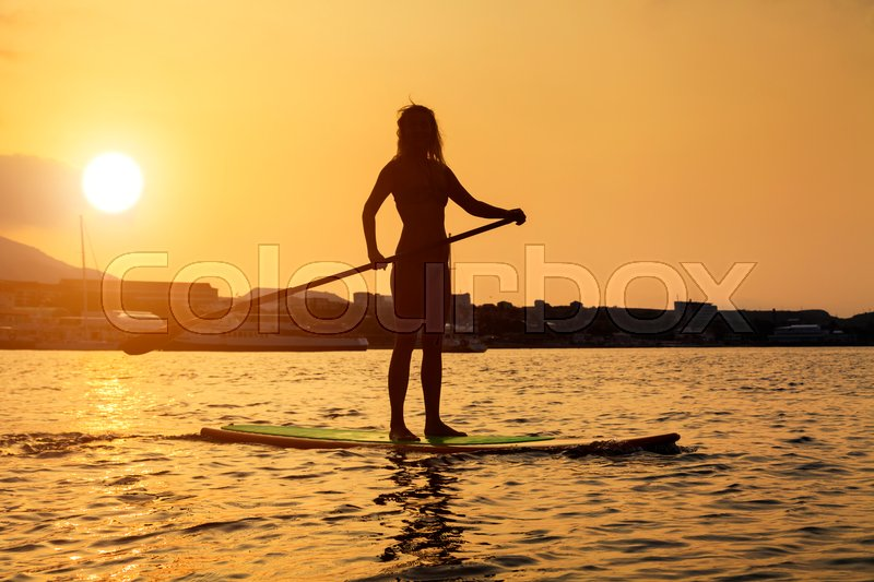 Silhouette of a beautiful woman on Stand Up Paddle Board. SUP, stock photo