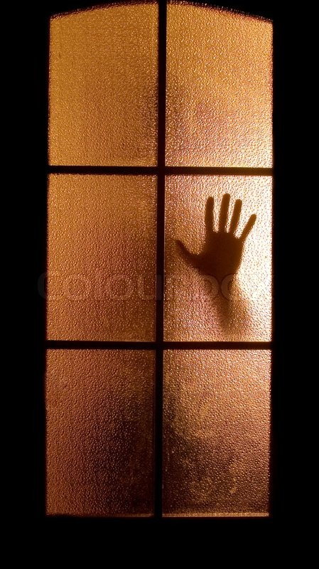 Slightly Blurred Silhouette Of A Hand Behind A Glass Door