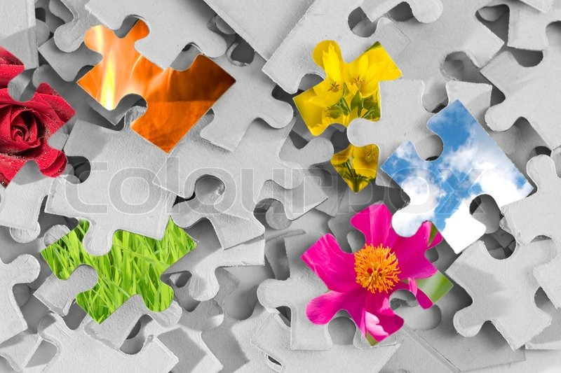 Pile of gray puzzle parts with several parts made as images of nature, stock photo