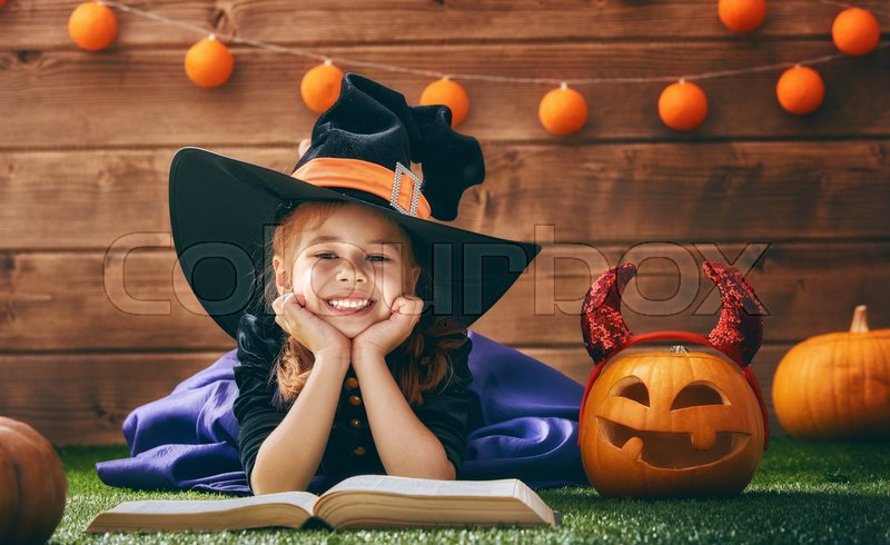 Happy Halloween! Cute cheerful little witch with a book of spells. Beautiful child girl in witch costume sitting on grass, reading and laughing, stock photo