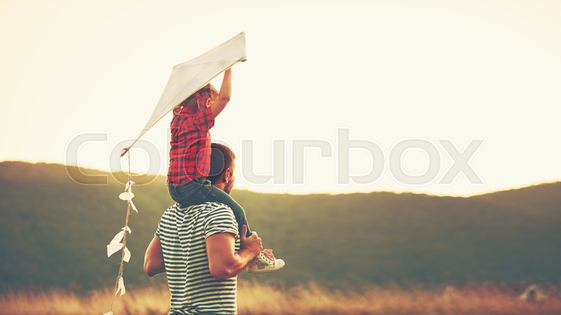 Happy family father and child on meadow with a kite in the summer on the nature, stock photo