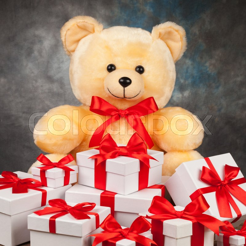Teddy bear and white boxes with gifts on the old board, stock photo