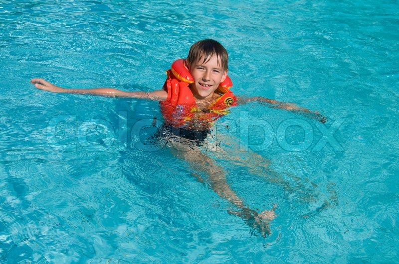 Boy In Life Jacket Is Learning To Swim In The Swimming Pool Stock Photo Colourbox