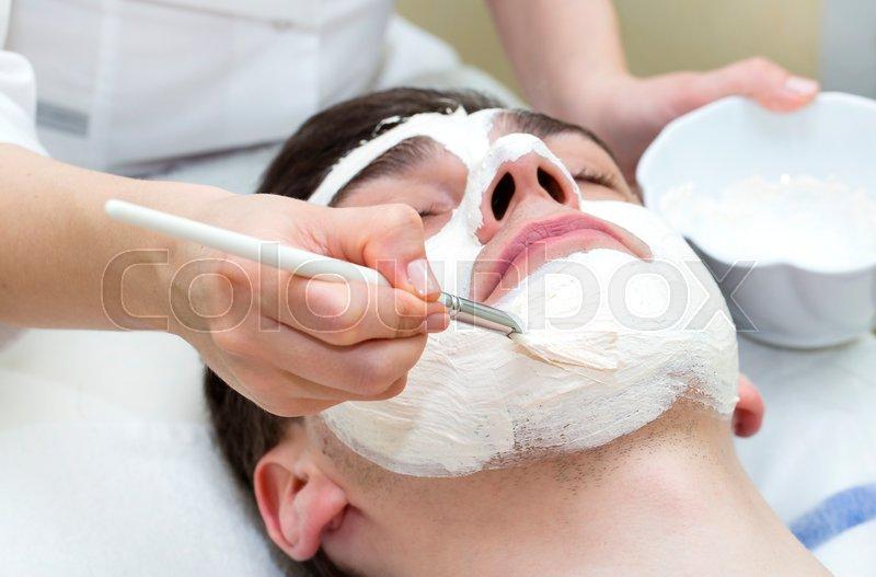Man in the mask cosmetic procedure in spa salon, stock photo