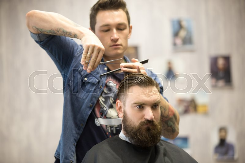 Portrait of handsome young bearded man getting trendy haircut in ...