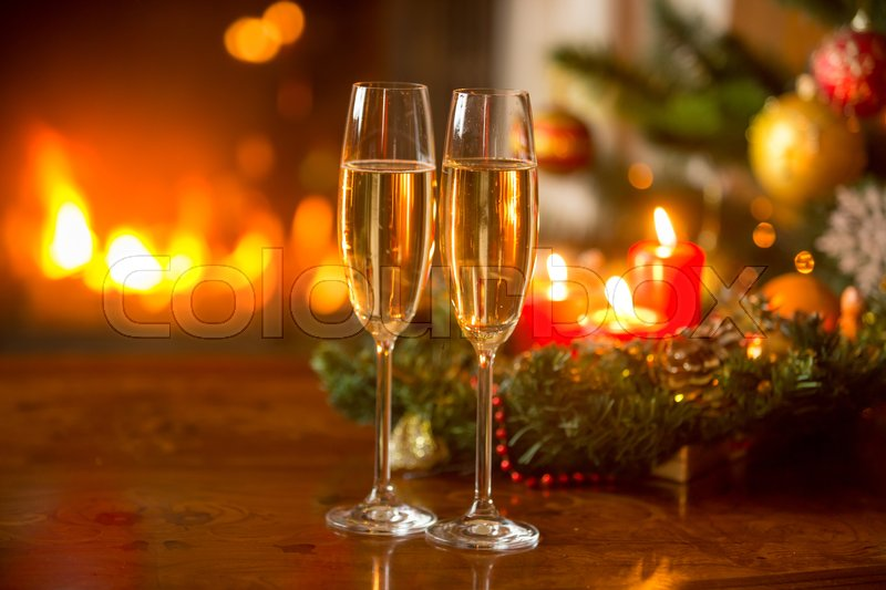 Beautiful Christmas background with two champagne flutes, burning fireplace and wreath with candles, stock photo