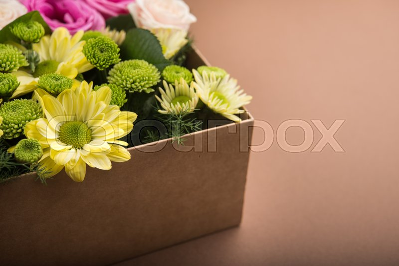 Gift box with flowers on vintage brown background, stock photo