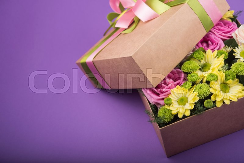 Gift box with flowers on purple background, stock photo