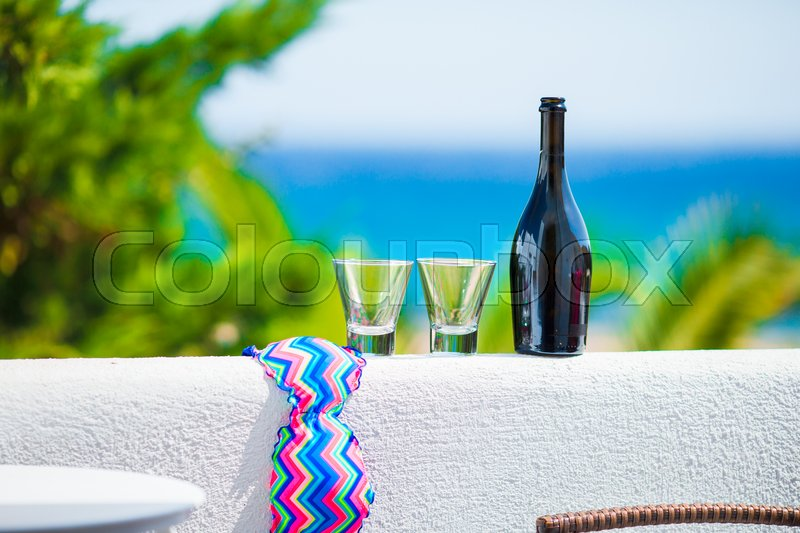 Glasses, bottle of tasty wine and swimsuit on balcony in greek island with view of sea, stock photo